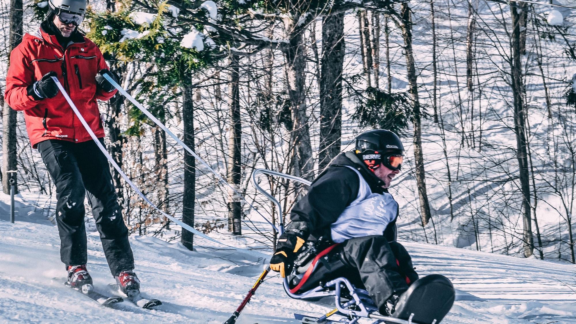 Un homme faut du ski assis, sécurité par Steve Charbonneau qui le suit dans la descente.