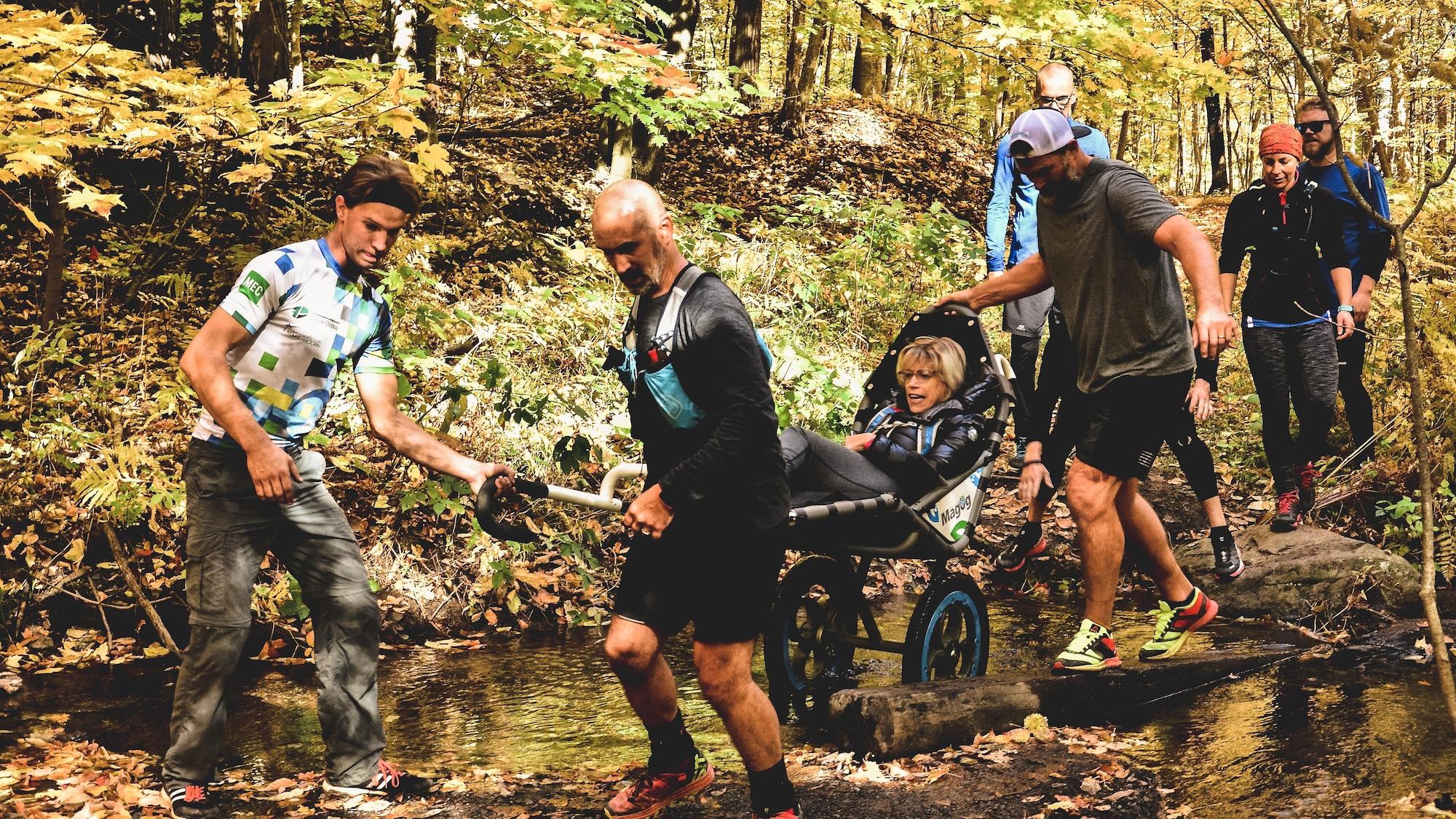 Steve Charbonneau et d'autres personnes aident une personne handicapée, assise dans un fauteuil roulant spécial, à se déplacer en forêt.