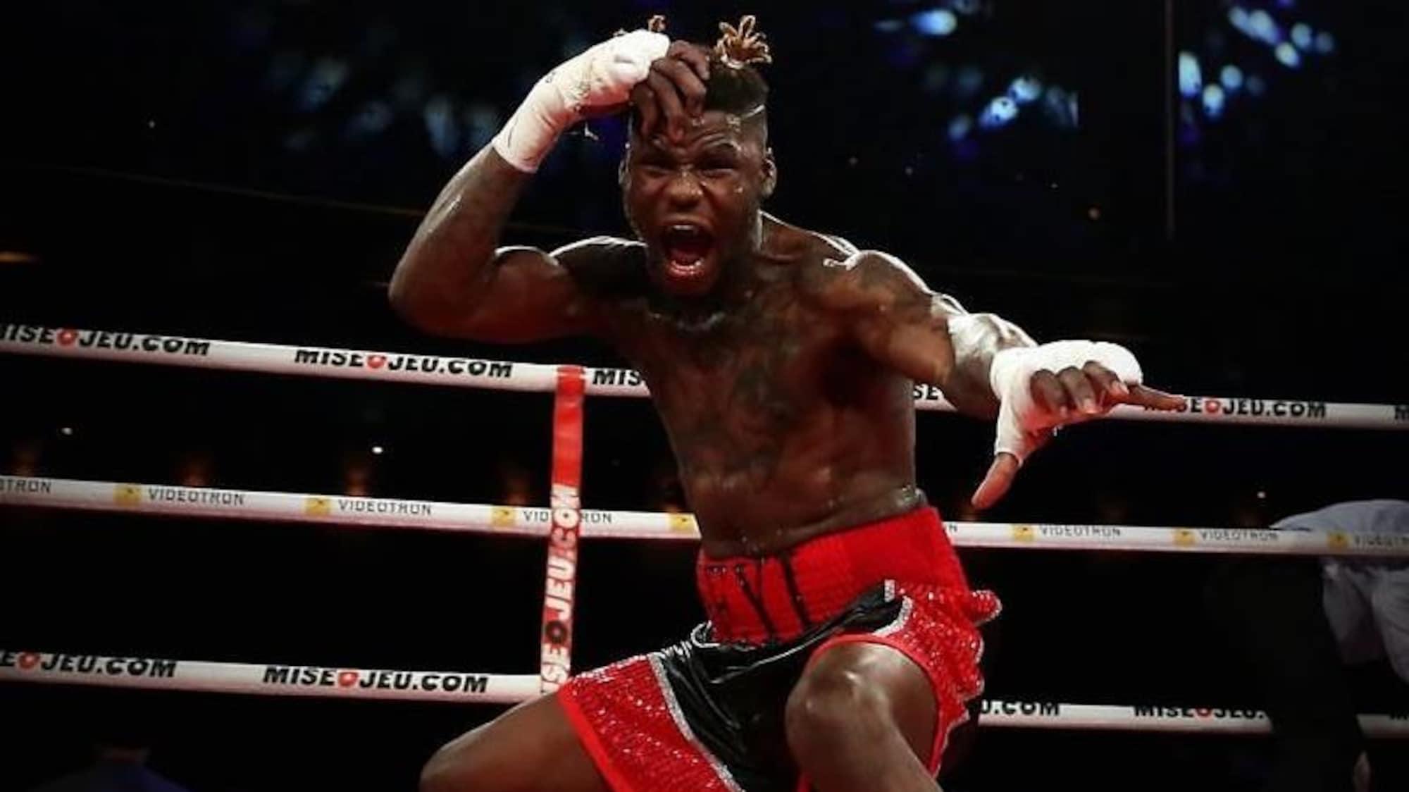 Il célèbre une victoire dans un ring de boxe.