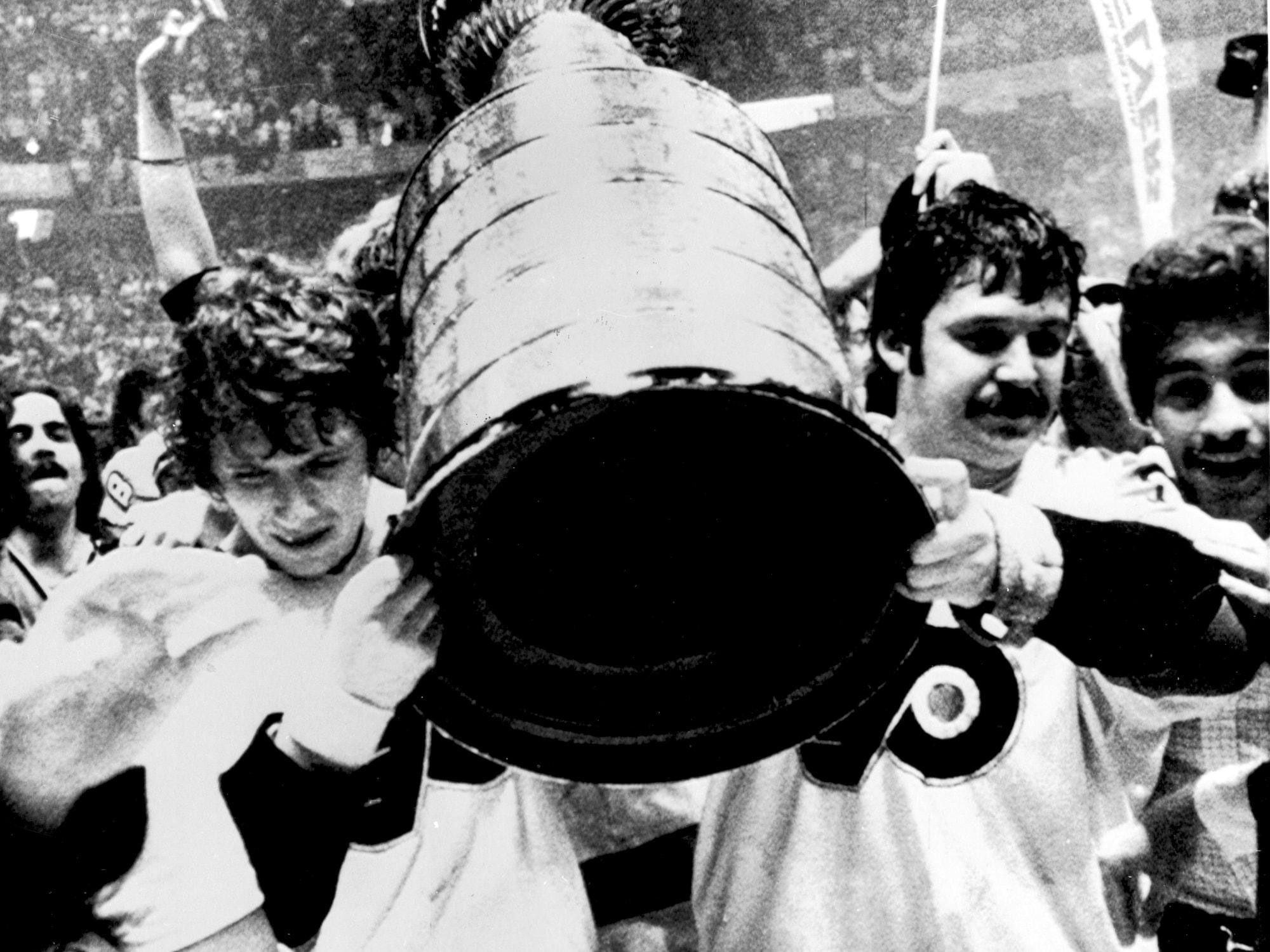 Bobby Clarke et Bernard Parent portent la coupe Stanley.