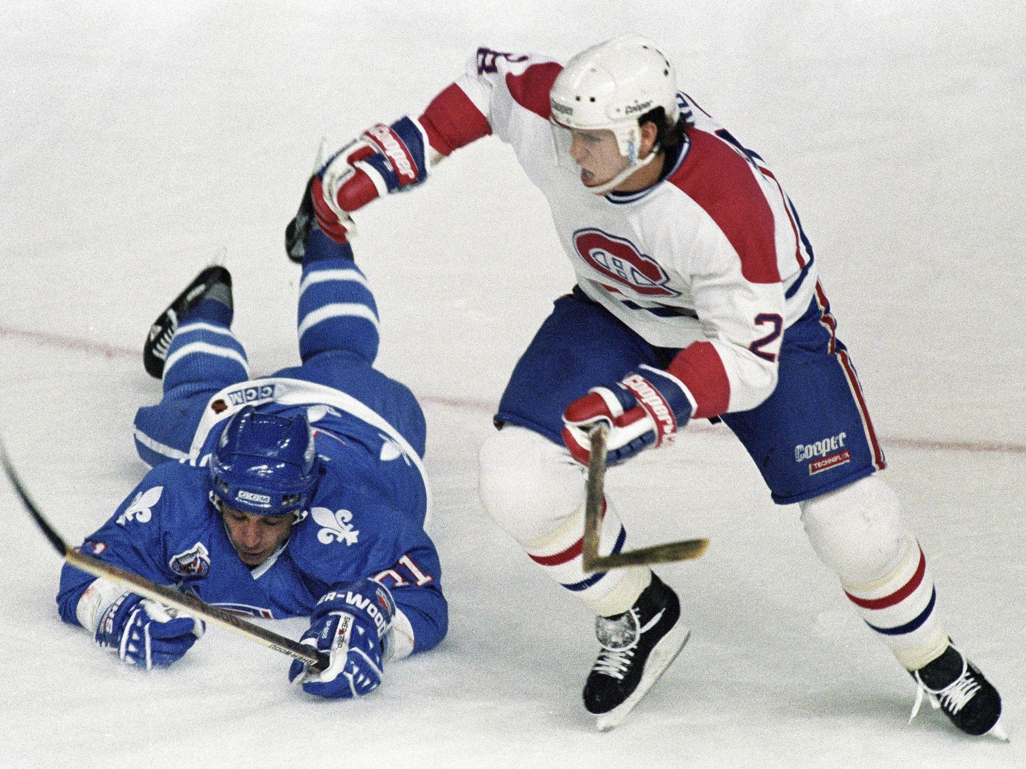 Valeri Kamensky, des Nordiques de Québec, tombe sur la glace en tentant de bloquer Éric Desjardins, du Canadien de Montréal.