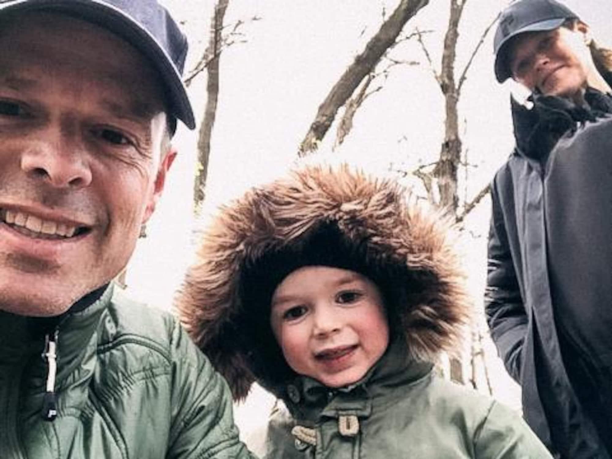 Jean-Luc Brassard, sa conjointe Shana et leur fils Grey sourient à la caméra lors d'une promenade en nature.