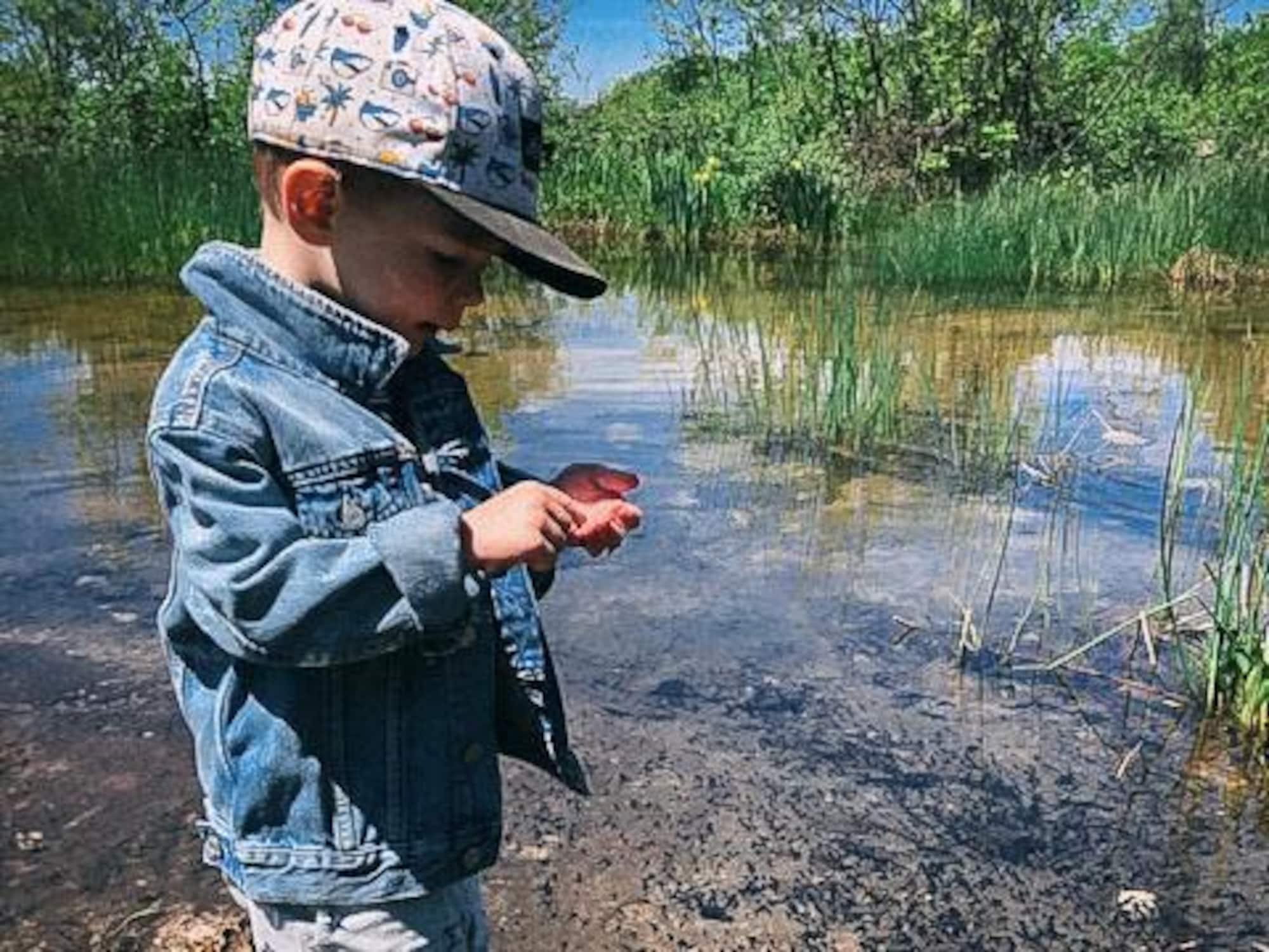 Grey, le fils de Jean-Luc Brassard, joue en bordure d'un cours d'eau.