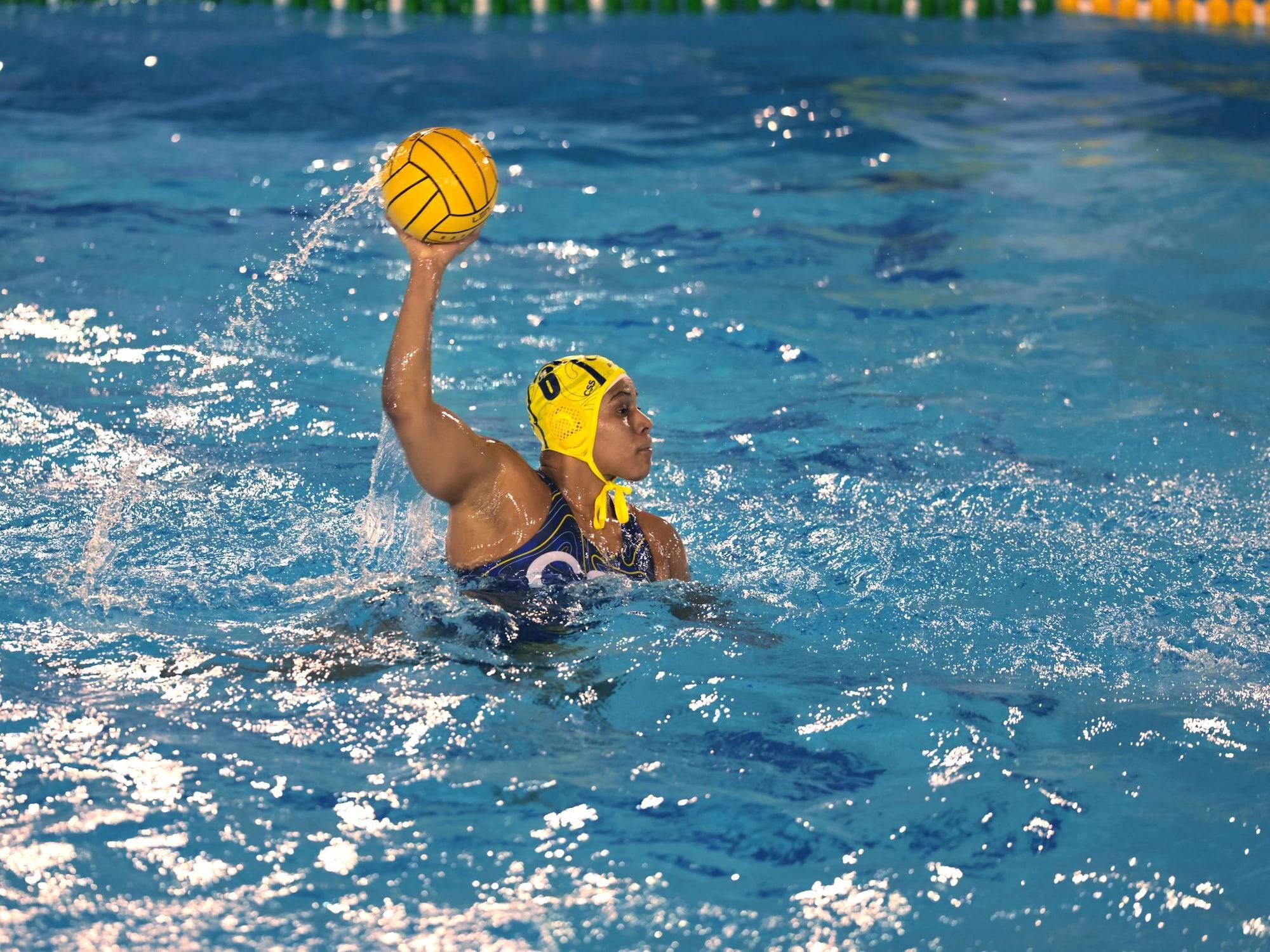 La joueuse de water-polo tient le ballon à bout de bras.