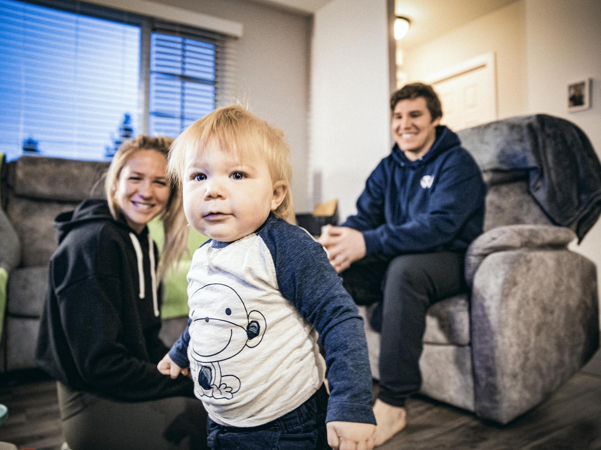 Marylou Dubé et Maxime St-Cyr regardent leur fils, dans leur salon.