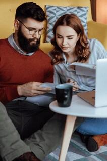 Un jeune couple regardent des états financiers devant un ordinateur.