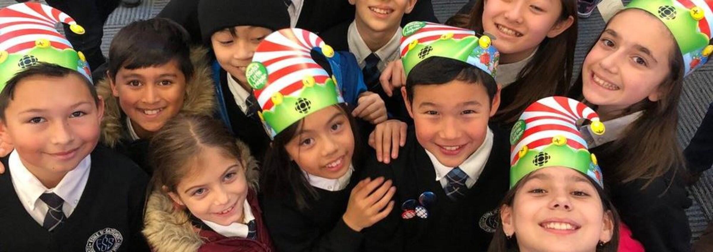Des enfants portent des bonnets de lutin en carton avec le logo de Radio-Canada.