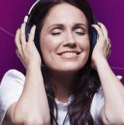 France Beaudoin écoute de la musique avec des écouteurs et sourit