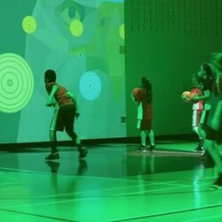 Des jeunes qui jouent au jeu avec un ballon sur le mur dans un gymnase.