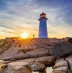 La photo d'un phare avec un coucher de soleil.