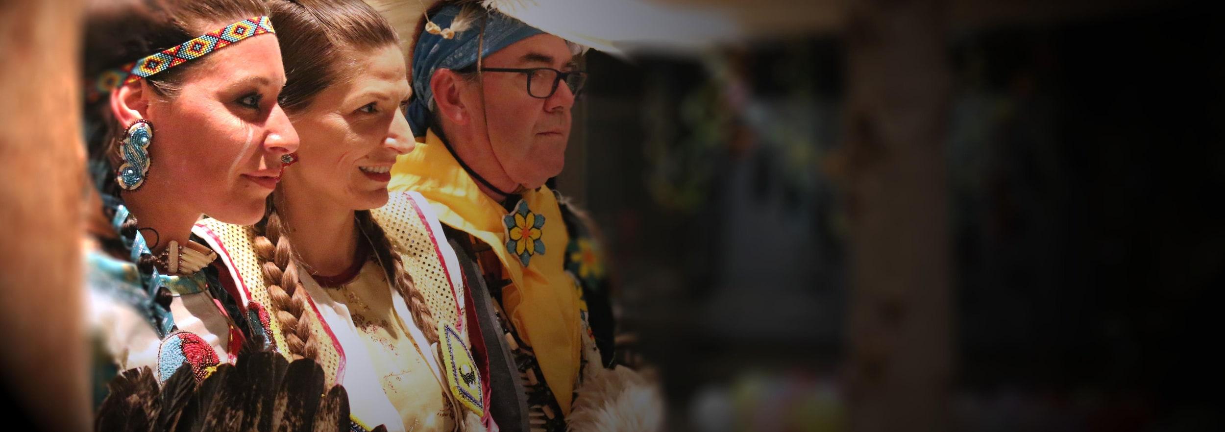 Trois danseurs de pow-wow (deux femmes et un homme) en habits traditionnels. Ils regardent tous vers la droite.
