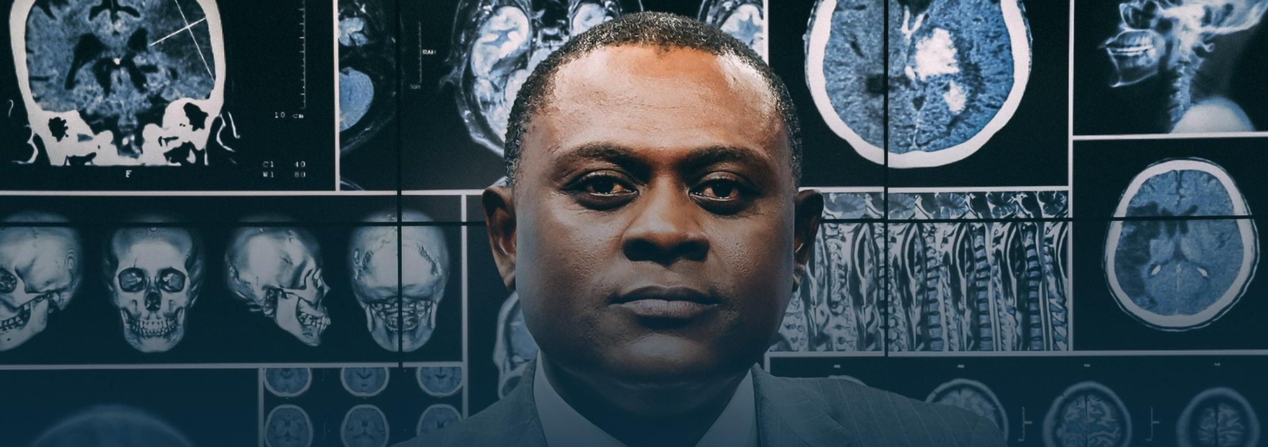 Le Dr Bennet Omalu se tient devant des planches de scans de cerveaux humains.