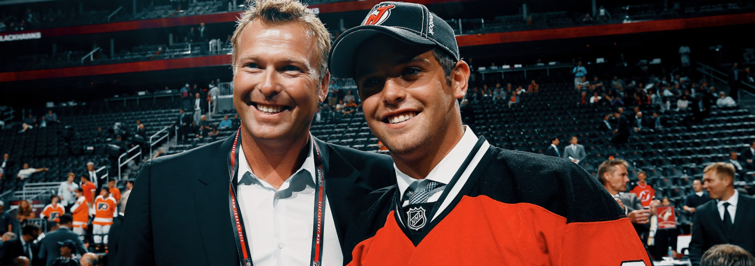 Anthony Brodeur, portant le chandail des Devils du New Jersey, se tient debout à côté de son père Martin.