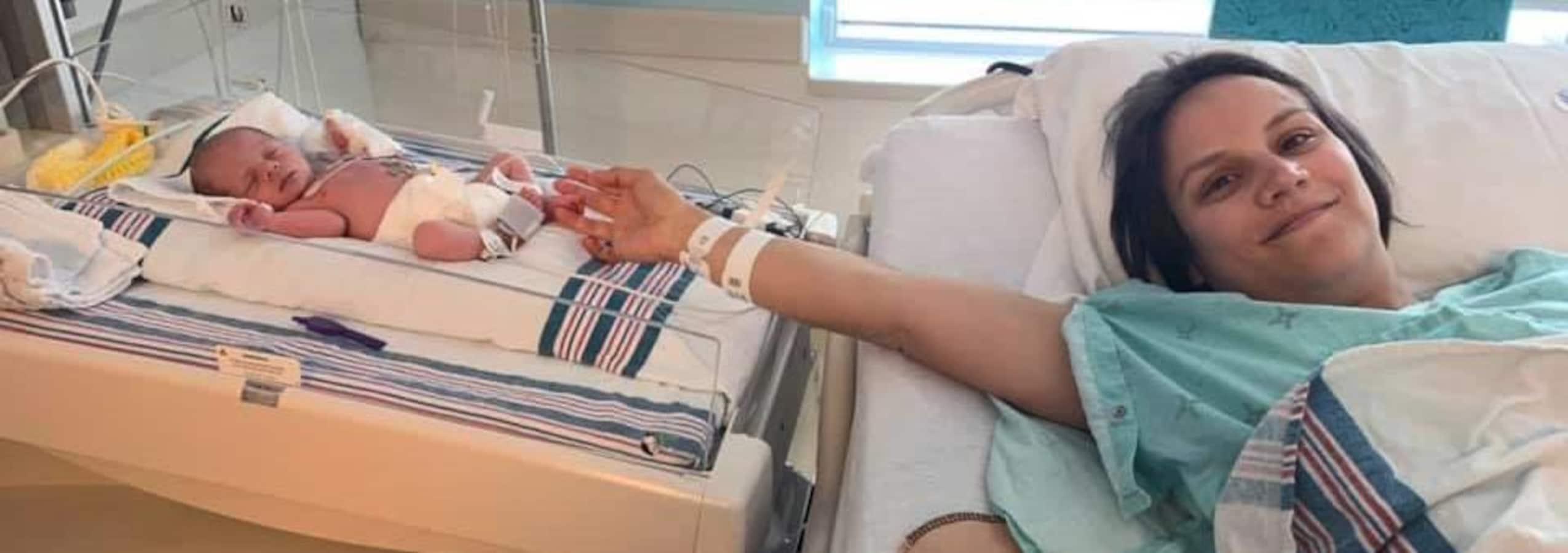Couchée dans son lit d'hôpital, Meagan Duhamel tend la main vers sa toute petite fille, qui dort juste à côté.