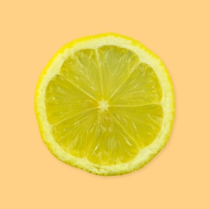 Une rondelle de citron sur un fond jaune.