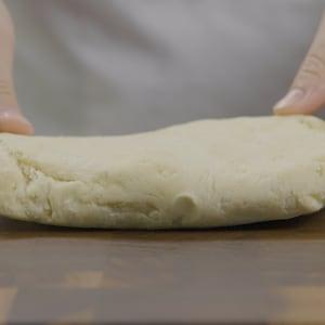 Un bloc de pâte est posé sur une planche à découper.