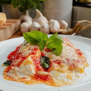 Deux cannellonis farcis, nappés de sauce tomate, gratinés et garnis de basilic frais.