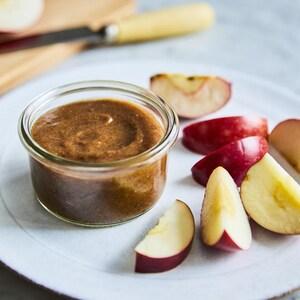 Un ramequin avec du caramel servi avec quelques tranches de pomme dans une assiette.