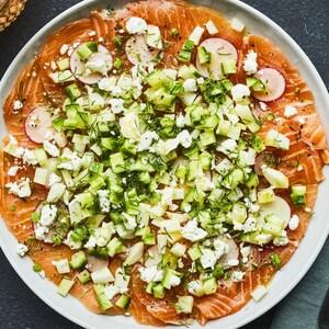 Une assiette de carpaccio de saumon garni de radis, de fenouil et de concombre.
