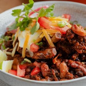 Un bol de chili con carne servie avec des herbes fraîches et des quartiers de lime.