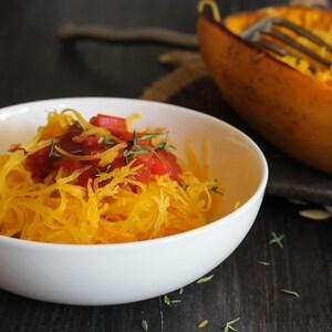 Un bol rempli de courge spaghetti avec un peu de sauce tomate.