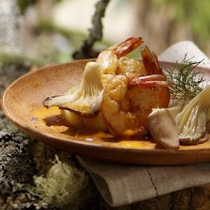 Deux crevettes cuites et deux pleurotes nappés d'une sauce légère orangée, et une branche d'anis, déposés dans une assiette brune.