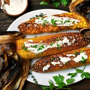 Des épis de maïs grillés avec leur feuille, de la mayo sur une assiette.