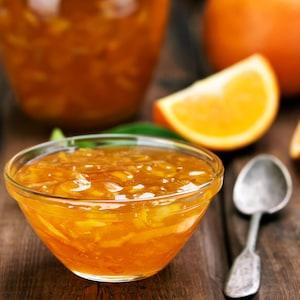 Un bol de marinade à la bière et à la marmelade avec des quartiers d'orange.