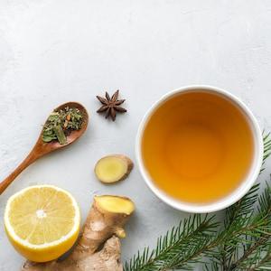 Un bol rempli de thé avec du citron, du gingembre et des épices sur la table.