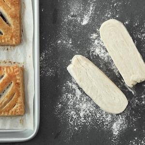 Deux chaussons aux pommes cuits sur une plaque sont placés près de deux morceaux de pâte.