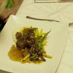 Une assiette de poitrine de porc croustillante et de légumes déposée sur une table devant un enfant.