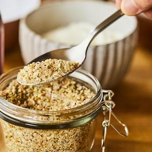 Mélange de grains entiers concassés dans un pot vitré.