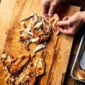 Deux mains effilochant des poitrines de poulet cuites.