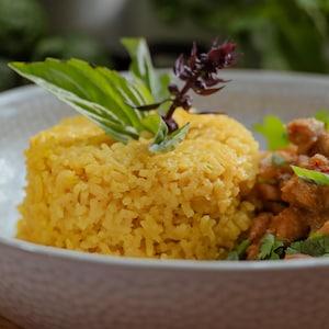 Une portion de riz servie aux côtés de cari rouge et garnie d'herbes fraîches.