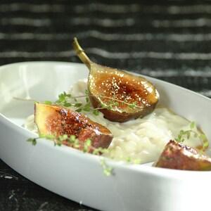 Un plat blanc avec du riz crémeux et des figues caramélisées.