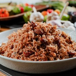 Un plat de riz aux pois, aux côtés de piments Scotch Bonnet et de gousses d'ail.