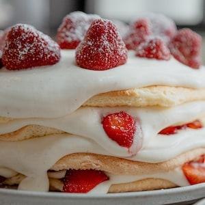 Des tranches de gâteaux étagés avec de la chantilly et des fraises.