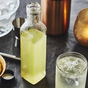 Du sirop dans une bouteille en vitre, un bol avec des citrons et des limes, un bol de glaçons, une bougie et 2 verres remplis.