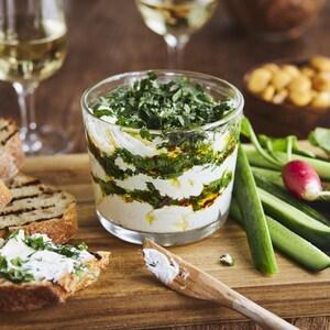 Tartinade étagée de fromage de chèvre aux herbes et à l'huile d'olive dans un plat en verre.