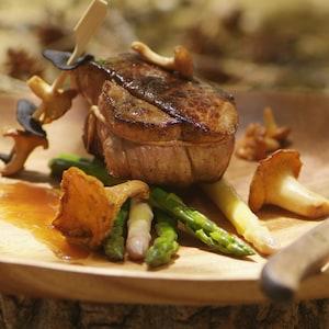 Une pièce de bœuf entourée de chanterelles, d'asperges blanches et vertes sur une planche de bois.