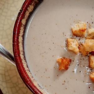 Un bol de velouté de chou-fleur et dattes, garni de croûtons.