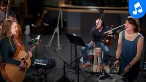 Les sœurs Boulay jouent du tambour et de la guitare et deux hommes derrière elles jouent du violon et de la contrebasse.