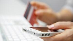 Une personne tient un téléphone et une carte de crédit.