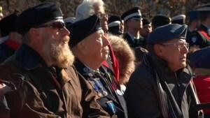 Des vétérans sont assis à l'extérieur, en uniforme, lors d'un défilé dans le cadre du jour du Souvenir.