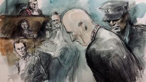 Photo d'un homme penché vers l'avant alors qu'un policier l'escorte à l'extérieur d'une salle de cour.