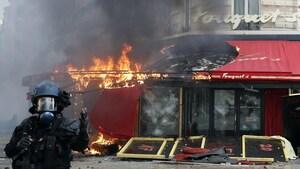 Un policier devant la devanture du restaurant Le Fouquet's, dont une partie est en place. On voit aussi vitres brisées.