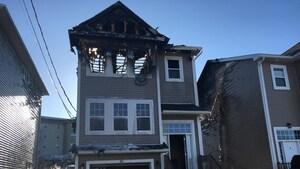 Le toit de la maison vue de face est en ruines, et les murs des deux maisons voisines sont endommagés.