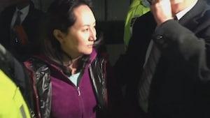 Une femme avec le visage éclairé par des lumières de caméra.