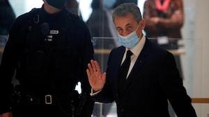 Nicolas Sarkozy salue de la main.