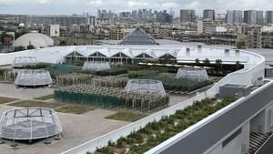 Des jardins sur un grand toit, et en arrière-plan de nombreux immeubles.